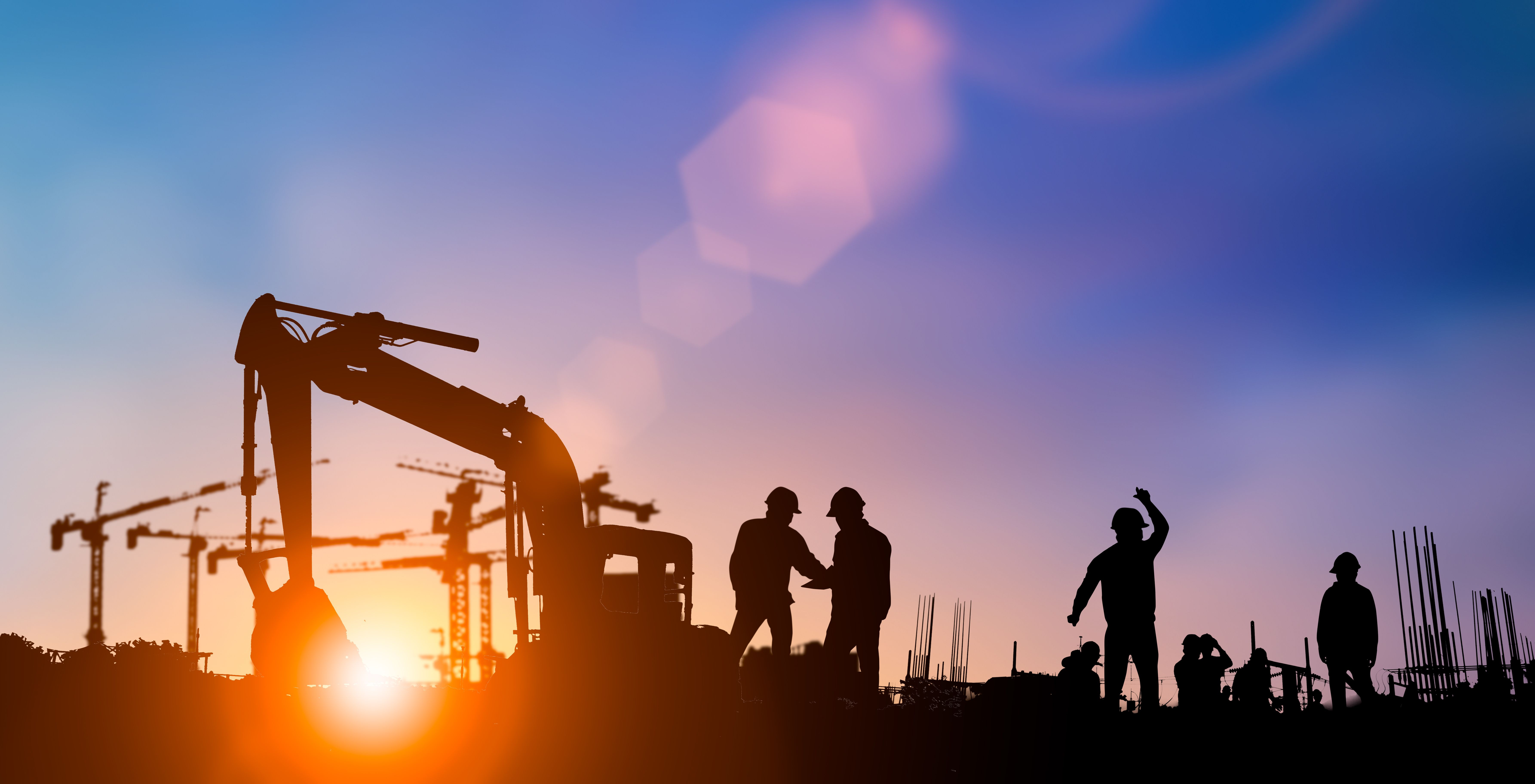 Silhouette of construction workers on site at sunrise